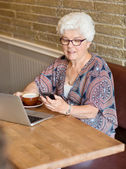 Woman Text Messaging Through Smartphone In Cafe — Stock Photo