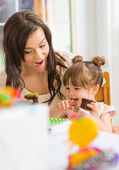 Mother Looking At Girl Eating Cupcake — Stock Photo