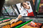 Saleswoman Picking Meat Displayed In Cabinet — Stock Photo