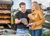 Couple Using Digital Tablet At Butcher's Shop — Stock Photo