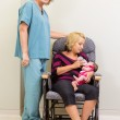 Nurse Standing By Mother Feeding Newborn Babygirl In Hospital — Stock Photo #36708543