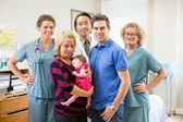 Medical Team With Newborn Baby Girl And Parents In Hospital — Stock Photo