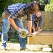 Carpenter Assisting Coworker In Cutting Wood With Handheld Saw — Stock Photo