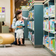 Teacher And Boy Selecting Book In Library — Stock Photo #36722691