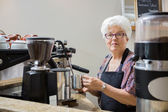 Senior Woman Steaming Milk with Espresso Machine — Stock Photo