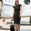Woman With Luggage Walking Against Private Jet — Stock Photo