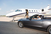 Pilot In Convertible Parked Against Private Jet — Foto de Stock