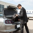 Stock Photo: BusinessmUnloading Luggage From Car At Airport Terminal