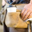 Stock Photo: Disposable Coffee Cup And Hammer On Carpenter's Tool Belt