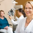 Stock Photo: Confident Optometrist With Colleague Examining Patient