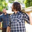 Stock Photo: Carpenter And Coworker Carrying Wooden Planks