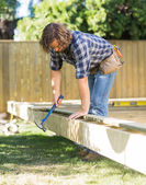Worker Using Hammer On Wooden Frame At Construction Site — Stock Photo