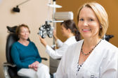 Confident Optometrist With Colleague Examining Patient — Stock Photo