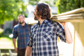 Carpenter And Coworker Carrying Wooden Planks — Stock Photo