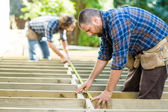 Carpenters Measuring Wood With Tape At Construction Site — Stock Photo