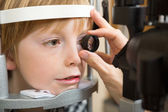 Optician's Hand Examining Boy's Retina — Stock Photo