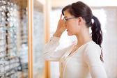 Femme qui tente de nouvelles lunettes au magasin d'opticien — Photo