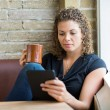 Woman Using Digital Tablet While Having Coffee In Cafe — Stock Photo #37384327