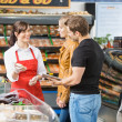 Saleswoman Assisting Couple In Buying Meat — Stock Photo