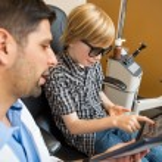 Boy Reading Test Chart While Optometrist — Stock Photo
