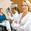 Confident Ophthalmologist With Colleague Examining Patient — Stockfoto