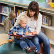 Teacher And Schoolboy Reading Book In Library — Stock Photo #37422429