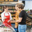 Saleswoman Assisting Couple In Buying Meat — Stock Photo #37422859