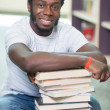 Smiling Student With Stacked Books Sitting In Library — Photo