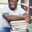 Smiling Student With Stacked Books Sitting In Library — Foto Stock