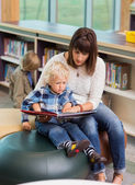 Teacher And Schoolboy Reading Book In Library — Stock Photo