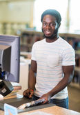 Librarian Scanning Books At Counter In Library — Stock Photo