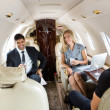 Business Professionals Having Drinks On Private Jet — Stock Photo