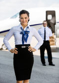 Confident Airhostess With Hands On Hip At Airport Terminal — Stock Photo
