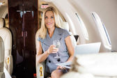 Businesswoman Having Wine In Corporate Jet — Stock Photo