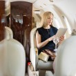Stock Photo: WomUsing Tablet Computer In Private Jet