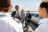 Business Professionals Greeting Pilot And Airhostess At Airport — Stock Photo