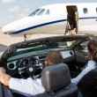 Постер, плакат: Pilot And Stewardess In Convertible Parked Against Private Jet