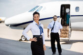 Confident Stewardesses Smiling With Pilot And Private Jet In Bac — Stock Photo