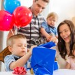 Family Looking At Birthday Boy Opening Gift Box — Stock Photo