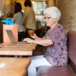 Senior Woman Using Laptop While Having Coffee In Cafeteria — Stock Photo #38325637