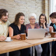 Woman With Friends Using Laptop At Coffeeshop — Stock Photo #38325923