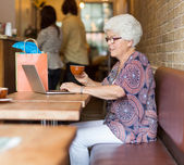 Senior Woman Using Laptop While Having Coffee In Cafeteria — Stock Photo