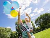 Mother And Daughter With Balloons In Park — Stock Photo