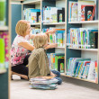 Teacher Assisting Boy In Selecting Books In Library — Photo