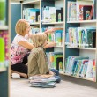 Teacher Assisting Boy In Selecting Books In Library — Zdjęcie stockowe