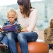 Teacher With Boy Reading Book In Library — Stock Photo #38384449