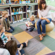 Teacher Reading Book To Children In Library — Stock Photo #38385531
