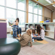 Постер, плакат: Teachers And Primary Students In Library