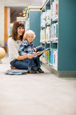 Happy Teacher And Boy Reading Book In Library — Stock Photo