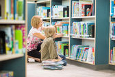 Teacher Assisting Boy In Selecting Books In Library — Stock Photo
